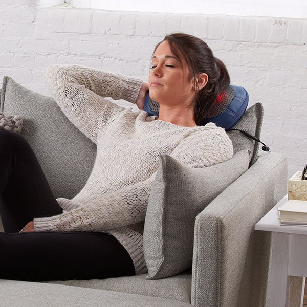 A women relaxed using a neck massager sitting on a couch.