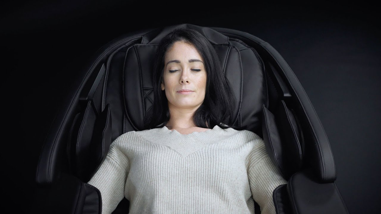Woman laying in a massage chair, with her eyes closed.