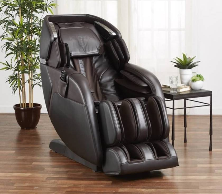 Black leather-upholstered massage chair in a room with white walls, hardwood floors and assorted plants.